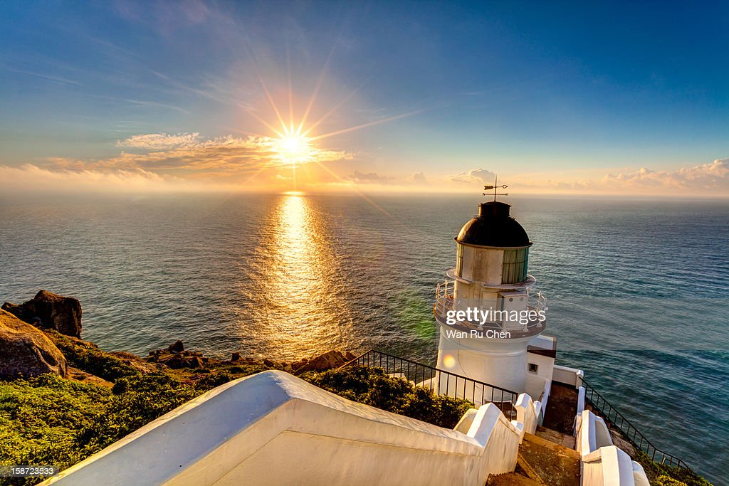 dramatic sky and lighthouse at sunrise : Stock Photo