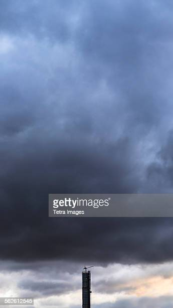 dramatic sky over skyscraper - moody sky stock pictures, royalty-free photos & images