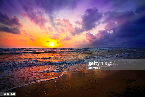 Dramatic sky reflection on a tropical beach at sunrise