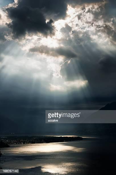 Dramatischer Himmel mit Sonnenstrahlen über Lago Maggiore, der Schweiz