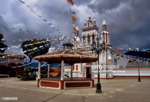 dramatic stormy clouds over the spanish colonial style church and music kiosk decorated with multi color flags during a local festival in the main square of the mexicanos neighborhood in san cristobal de las casas, chiapas, mexico - victor ovies fotografías e imágenes de stock