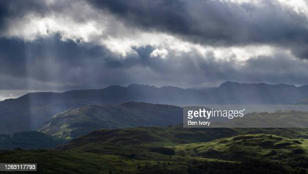 dramatic stormy skies over lake district mountains towards tarn hows - rain stock pictures, royalty-free photos & images