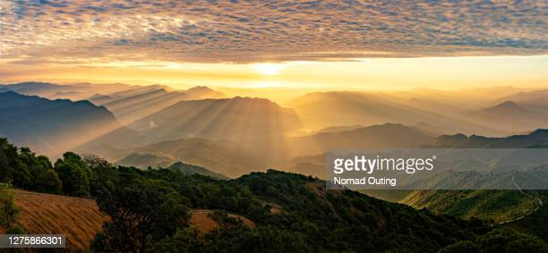 dramatic sunrise and sunset with clouds on the sky over mountain range. - majestic stock pictures, royalty-free photos & images