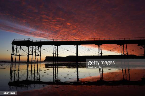 Dramatic sunrise starts the day above Saltburn pier on October 27, 2020 in Saltburn By The Sea, England.