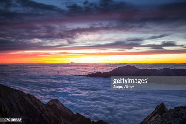 dramatic sunset behind kasagadake and nuketo mounts surrounded by low clouds - 岐阜県 ストックフォトと画像