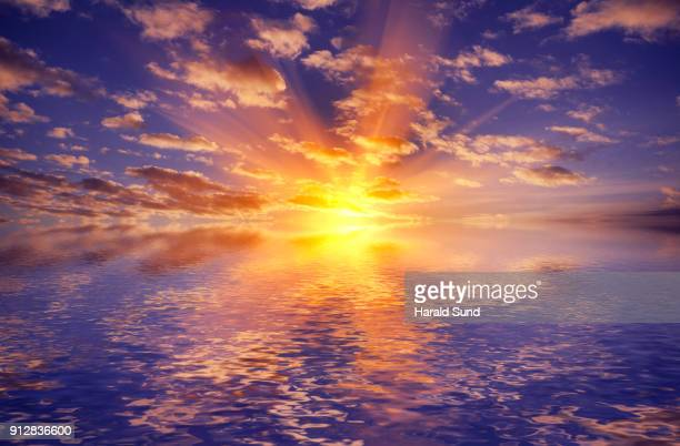 Dramatic sunset in a dark blue sky illuminating clouds reflected in the calm waters of a lake.