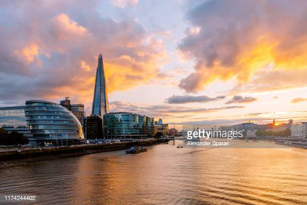 dramatic sunset in london with thames river, shard skyscraper and london city hall, england, uk - shard london bridge stock pictures, royalty-free photos & images