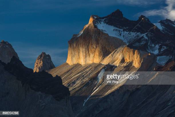 Dramatic sunset light illuminates the yellow granite face of Monte Almirante Nieto A cloud casts a shadow creating a dark band across the face To the...
