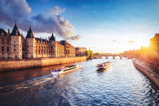 Dramatic sunset over river Seine in Paris, France, with Conciergerie and cruise boats. 863383050