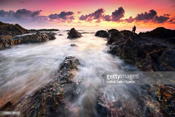 dramatic sunset over the rocky beach - rocky coastline stock pictures, royalty-free photos & images