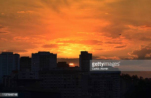 dramatic sunset sky and helicopter in the distance - carlos alkmin stock pictures, royalty-free photos & images