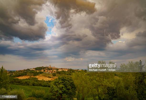 dramatic sunset sky over san gimignano, tuscany - michael stock photos and pictures