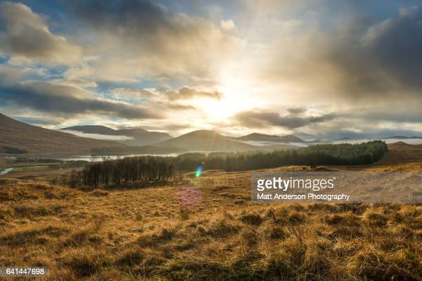 Dramatic sunset with atmospheric clouds over the mountainous Scottish landscape.