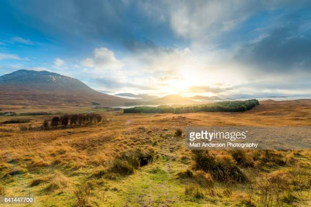 dramatic sunset with atmospheric clouds over the mountainous scottish landscape. - 荒野 ストックフォトと画像