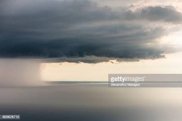 Dramatic thunder cloud with rain shaft over the ocean