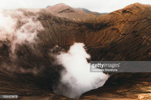dramatic view of bromo volcano erupting during sunrise in indonesia - bromo tengger semeru national park stock pictures, royalty-free photos & images