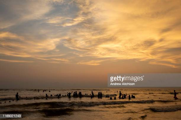 Dramatic wispy clouds in the sky above groups of people swimming in the Bay of Bengal sea during sunset on Laboni Beach Cox Bazar Chittagong Division...