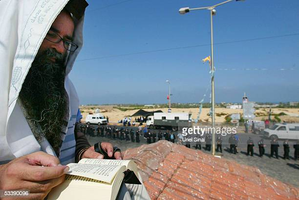 Draped in a prayer shawl an opponent of the disengagement plan reads from a prayer book on a rooftop as Israeli troops are deployed below August 15...
