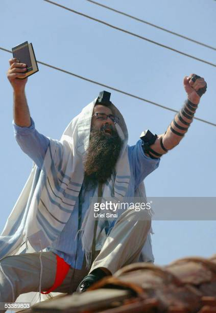 Draped in a prayer shawl and carrying a prayer book an opponent of the disengagement plan shouts against Israeli troops August 15 2005 in the Israeli...
