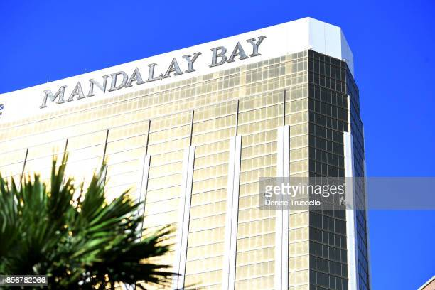 Drapes blow through two broken windows on the 32nd floor of the Mandalay Bay Resort and Casino where a gunman reportedly opened fire through the...