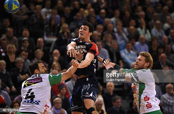 Drasko Nenadic of Flensburg is challenged by Manuel Späth and Tim Kneule of Goeppingen during the DKB Bundesliga handball match between SG...