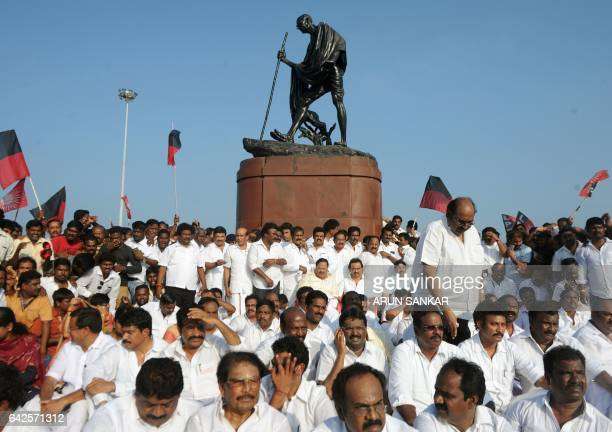 Dravida Munnetra Kazhagam party leader MK Stalin sits at a protest in front of a statue of Indian independence icon Mahatma Gandhi along with fellow...