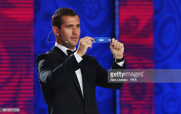 Draw assistant Alexander Kerzhakov holds up the name Israel during the European Zone draw at the Preliminary Draw of the 2018 FIFA World Cup in...