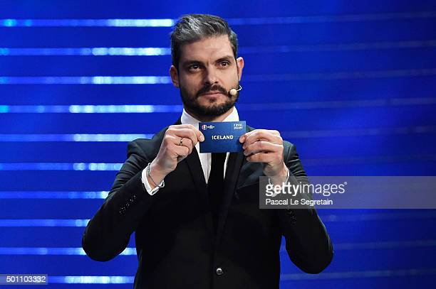 Draw assistant Angelos Charisteas draws out Iceland in to Group F during the UEFA Euro 2016 Final Draw Ceremony at Palais des Congres on December 12...