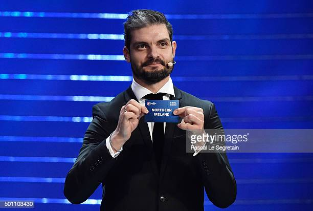 Draw assistant Angelos Charisteas draws out Northern Ireland in to Group C during the UEFA Euro 2016 Final Draw Ceremony at Palais des Congres on...