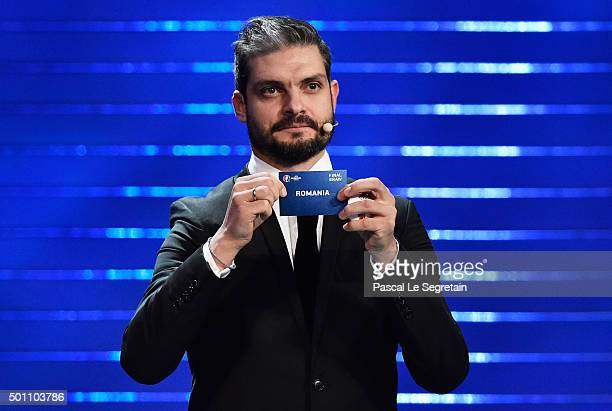 Draw assistant Angelos Charisteas draws out Romania in to Group A during the UEFA Euro 2016 Final Draw Ceremony at Palais des Congres on December 12...