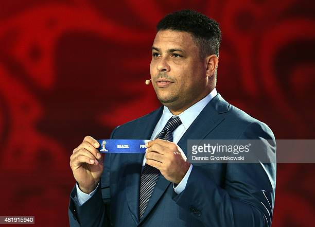 Draw assistant Ronaldo holds up the name Brazil during the South American Zone draw at the Preliminary Draw of the 2018 FIFA World Cup in Russia at...