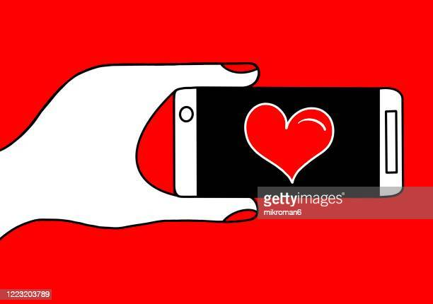 drawing a hand holding a smartphone with heart - mobile app stock pictures, royalty-free photos & images