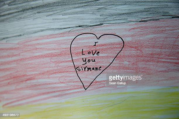 A drawing done by a migrant child shows the German flag and reads 'I love you Girmane' at a temporary shelter for migrants on October 17 2015 in...