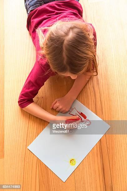 Drawing girl lying on wooden floor