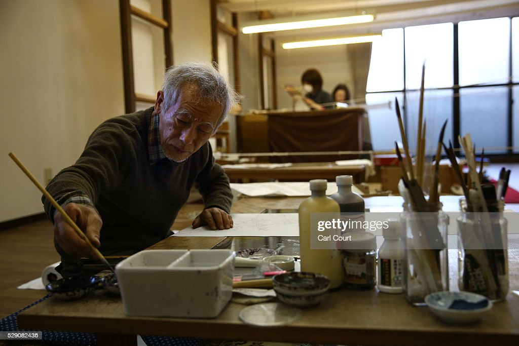 Drawing master Kenji Suhara draws the outline of designs on kimono fabric during a stage of its production process at the Sensyo Ichikawa kimono workshop on April 26, 2016 in Kyoto, Japan. The workshop employs a traditional method of dyeing called Kyo-Yuzen. Unique to Kyoto it is used to dye silk fabric for kimonos by hand-painting with natural dyes made from flower petals. The technique can be divided into 26 processes and each part is handled by the master of that process.
