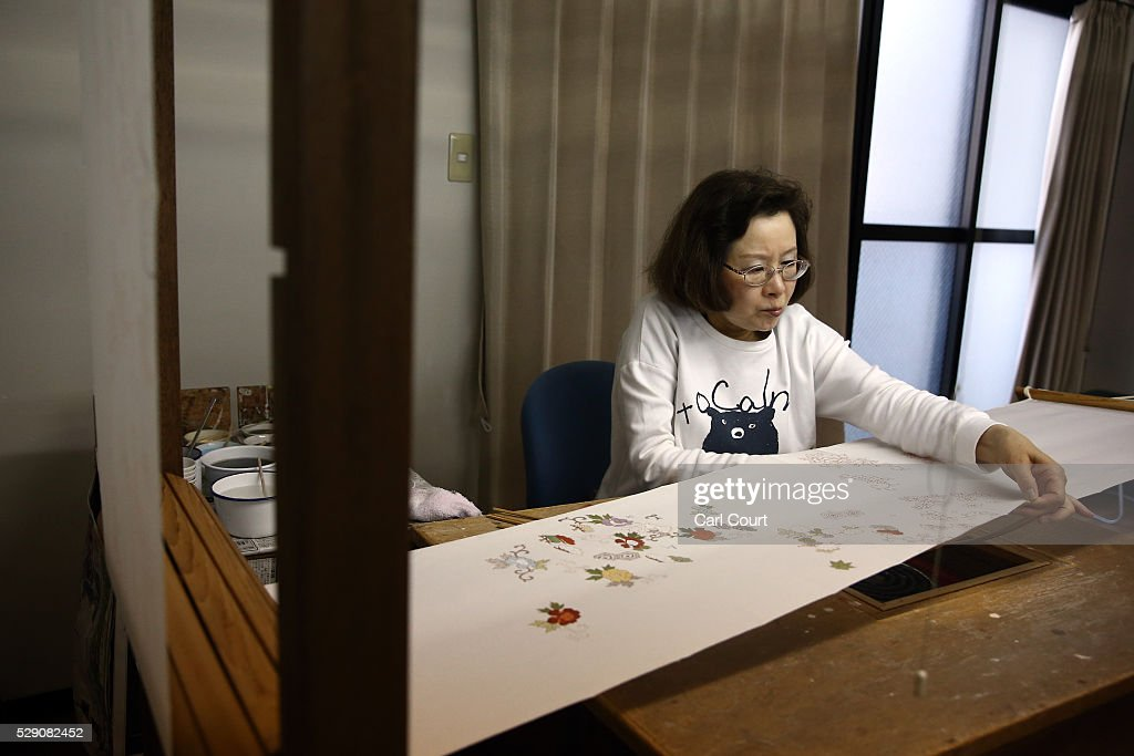 Drawing master Takako Yoshida paints a design on kimono fabric during a stage of its production process at the Sensyo Ichikawa kimono workshop on April 26, 2016 in Kyoto, Japan. The workshop employs a traditional method of dyeing called Kyo-Yuzen. Unique to Kyoto it is used to dye silk fabric for kimonos by hand-painting with natural dyes made from flower petals. The technique can be divided into 26 processes and each part is handled by the master of that process.