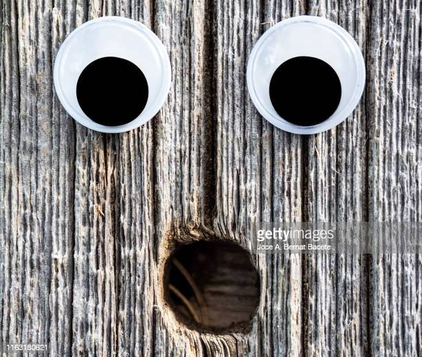drawing of a face and smiling eyes on a old wooden door. - comedian stock pictures, royalty-free photos & images