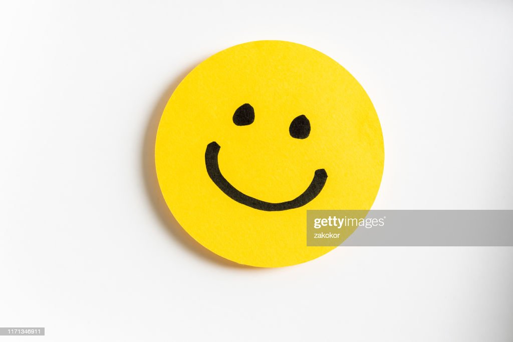 Drawing of a happy smiling emoticon on a yellow paper and white background. : Stock Photo