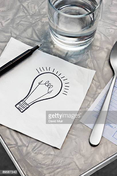 drawing of a light bulb on a table napkin - paper napkin stock photos and pictures