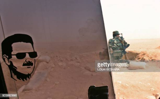 A drawing of Syrian President Bashar Assad is stamped on a car window through which a Syrian soldier is seen manning a border post in the desert on...