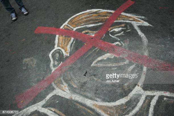 A drawing of US President Trump on a street as he visits the Philippines on November 14 2017 in Manila Philippines Hundreds of Filipinos protested in...