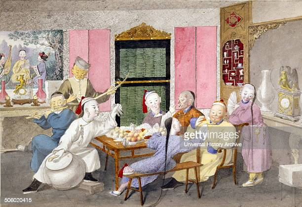 Drawing shows two older gentlemen seated at the head of a table being served by three young servants while three musicians accompany the feast in a...