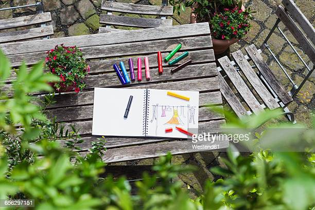 Drawing, sketch book with womans drawing and coloring pencils on wooden garden table