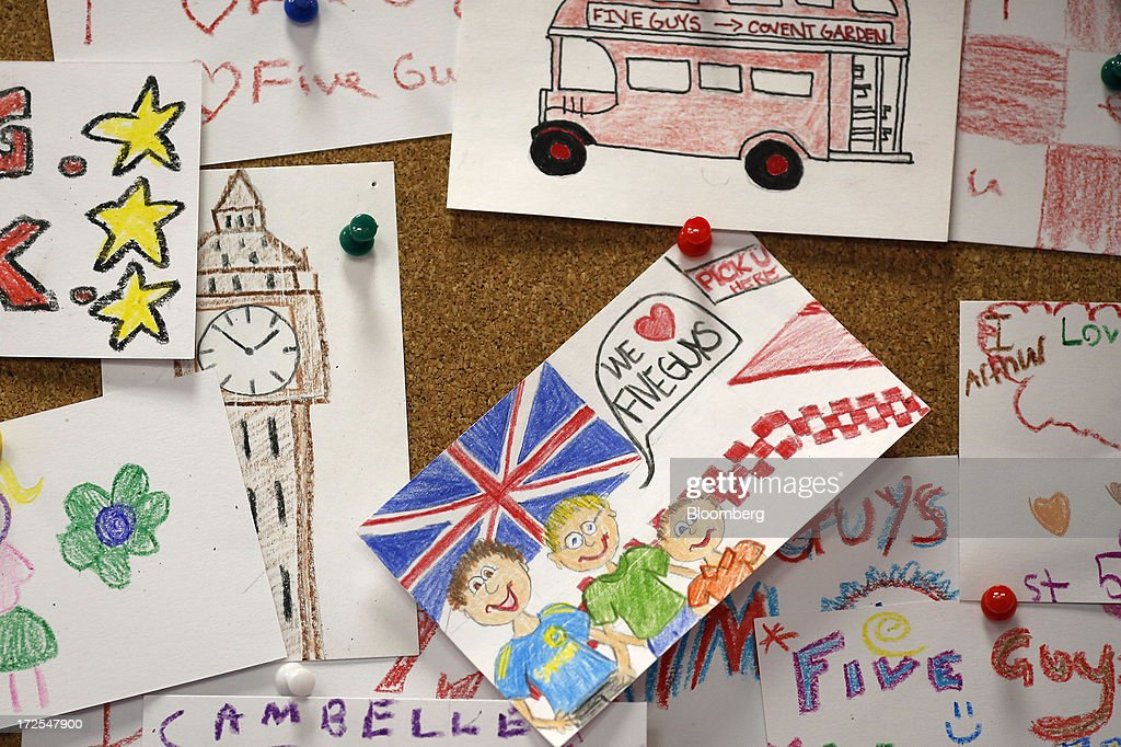 Drawings depicting British items, including a London bus, and Big Ben, are seen on a pin board inside U.S. burger restaurant chain Five Guys's new outlet in London, U.K., on Tuesday, July 2, 2013. Five Guys, which is set to open its first U.K. store in Covent Garden on July 4, is a family outfit that started in Washington, D.C., in 1986, and has expanded to more than 1,000 locations in the U.S. and Canada. Photographer: Simon Dawson/Bloomberg via Getty Images