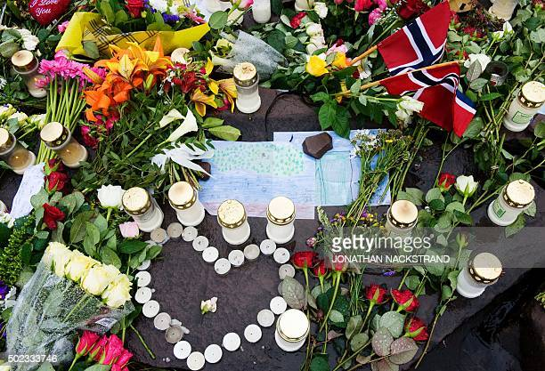 Drawings showing the Utoeya island tragedy are placed on July 26 2011 between flowers and candles on the edge of lake Tyrifjorden infront of the...