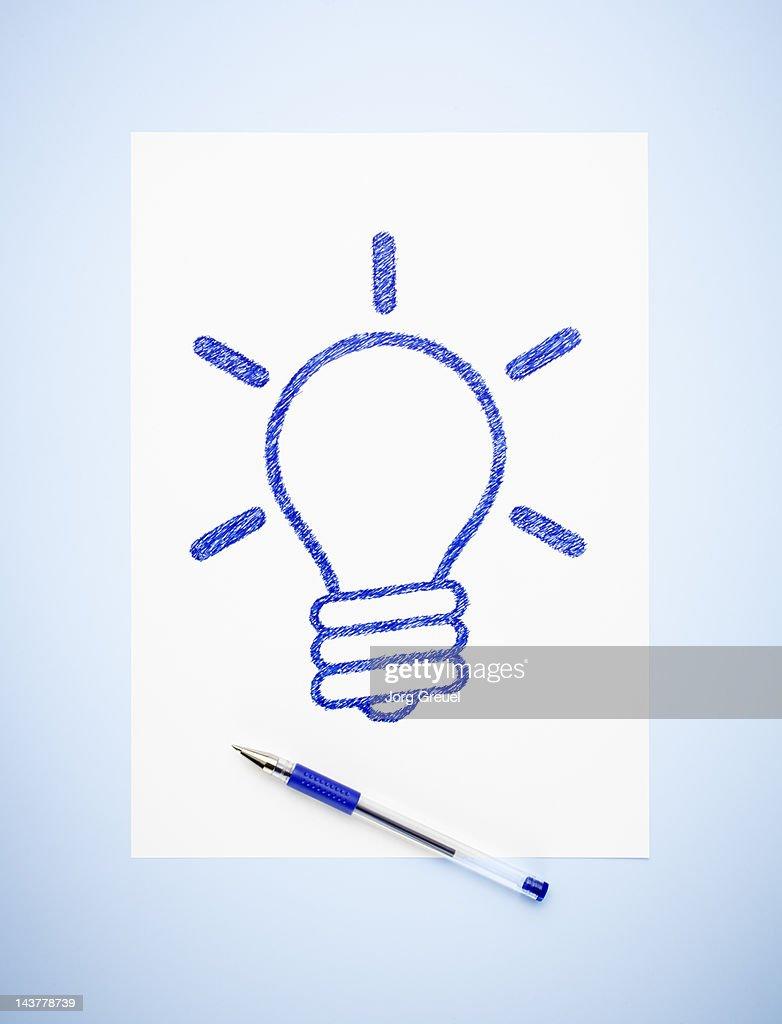 A drawn light bulb on a paper sheet : Stock Photo