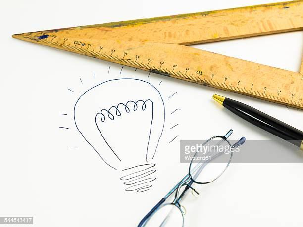 Drawn lightbulb, set square, reading glasses and ballpen on white paper