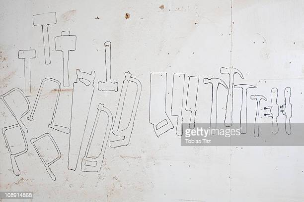 Drawn outlines of hand tools on a wall