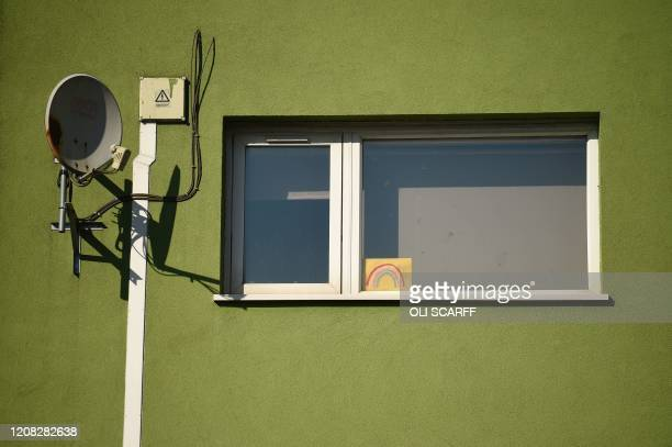 A drawn rainbow symbol of solidarity with the coronavirus lockdown is seen in the window of a house in Oldham northwest England on March 26 2020 The...