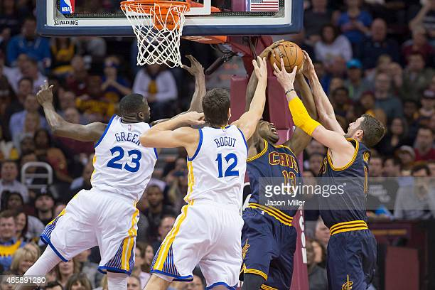 Draymond Green and Andrew Bogut of the Golden State Warriors fight Tristan Thompson and Kevin Love for a rebound during the first half at Quicken...